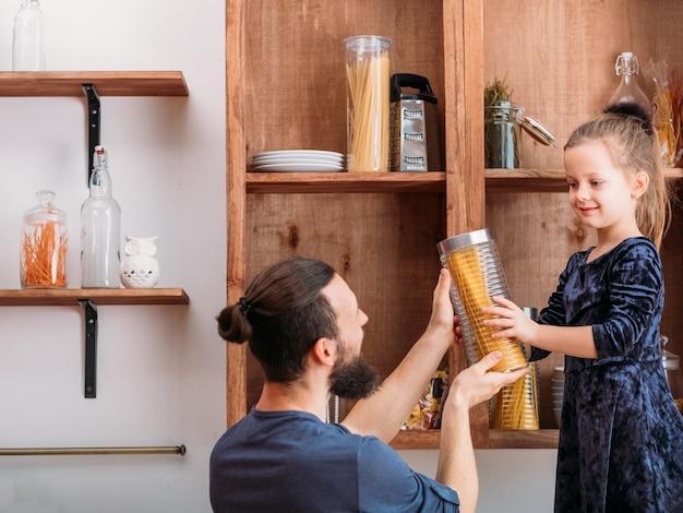 Familie vrijetijdsbesteding. vader en zijn schattige dochtertje genieten van samen thuis koken.