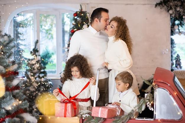 Familie wachten op kerstmis thuis in de buurt van kerstbomen.