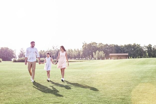 Familie wandeling gezin van drie wandelen op grasveld glimlachend hap