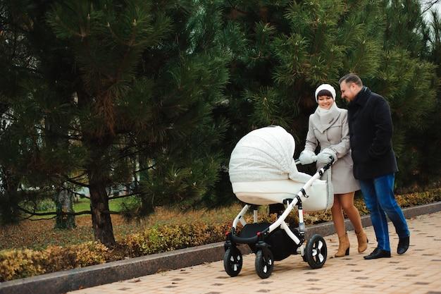 Familie wandeling in het najaar park met een kinderwagen. mama, papa en baby