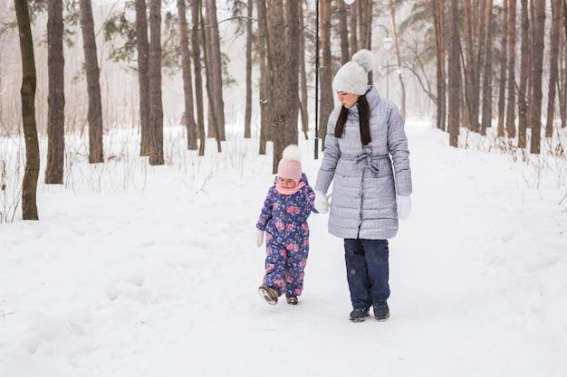 Familie-, winter- en natuurconcept - jonge vrolijke moeder met schattige dochtertje wandelen in de