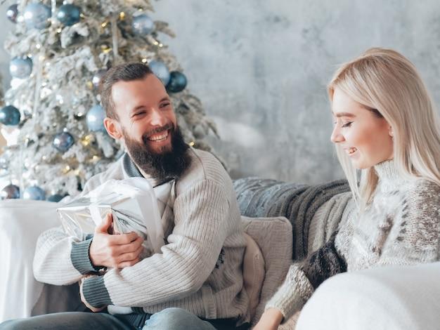 Familie wintervakantie. kerel is blij om een geschenk van zijn vriendin te ontvangen