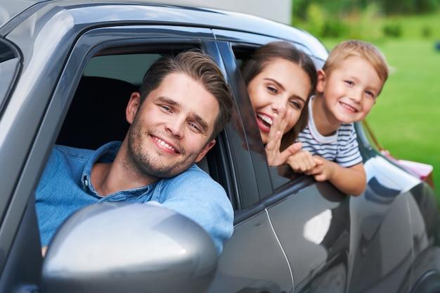 Familie zit in de auto en kijkt uit de ramen