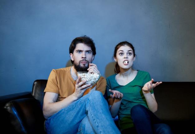 Familie zit 's avonds op de bank tv te kijken met popcorn-entertainment