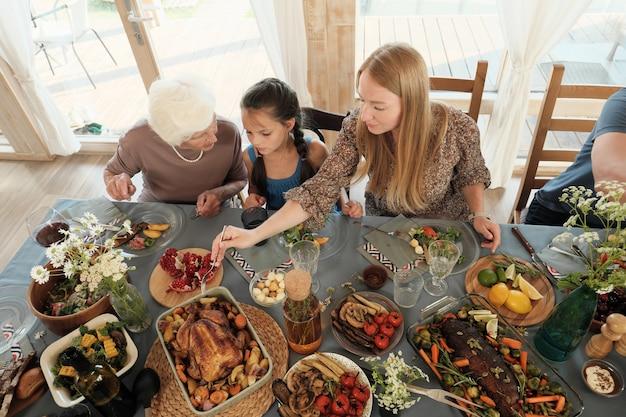 Familie zittend aan tafel en verschillende gerechten eten tijdens het vakantiediner thuis