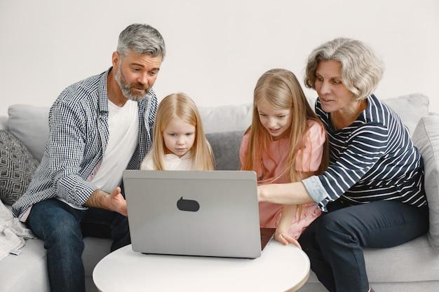 Familie zittend op de bank. volwassen man en vrouw spelen spelletjes met kleindochters in laptop. technologieën concept.