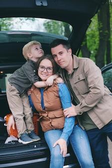 Familie zittend op de rand van de open kofferbak van hun auto
