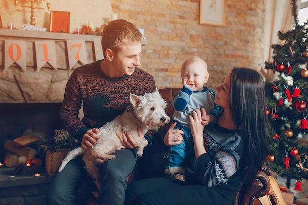 Familie zittend op een bank met een hond bij kerstmis
