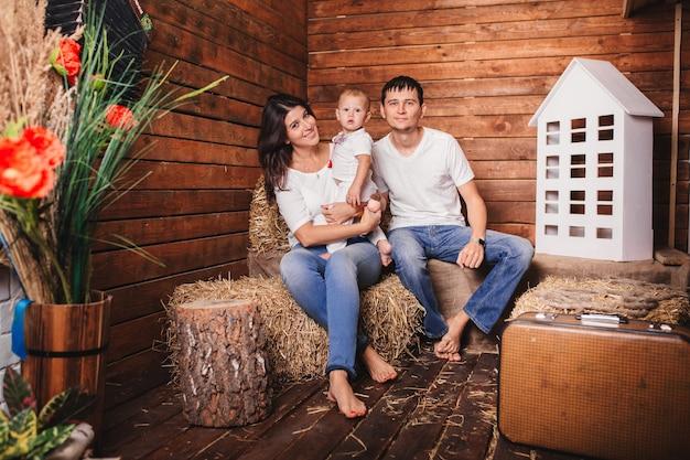 Familie zittend op een hooiberg op de achtergrond van de decoratiestudio. ouders met kind zoon samen plezier. leuke familie geniet van het rustieke zomerse leven.