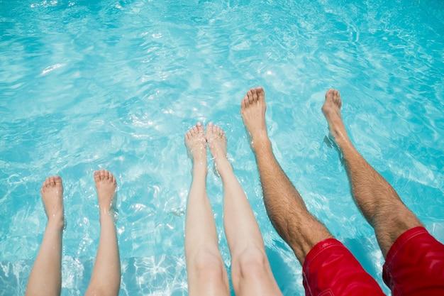 Familie zittend op het zwembad en hun benen schudden in zwembadwater