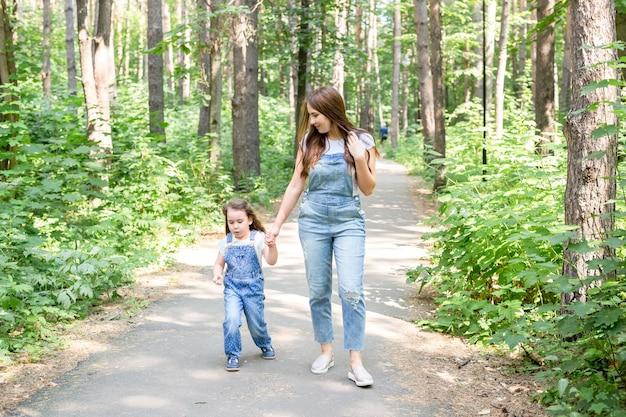 Familie-, zomer- en natuurconcept - aantrekkelijke jonge vrouw en mooi dochtermeisje die in groen park lopen.
