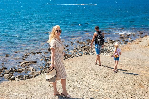 Familie zomervakantie aan zee. de vrouw wendde zich tot de camera, de man en het kind lopen langs de kust met een rugzak. reizen en toerisme.