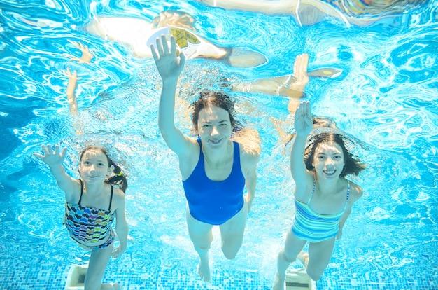 Familie zwemt in het zwembad onder water, gelukkige actieve moeder en kinderen hebben plezier onder water, fitness en sport met kinderen op zomervakantie op resort