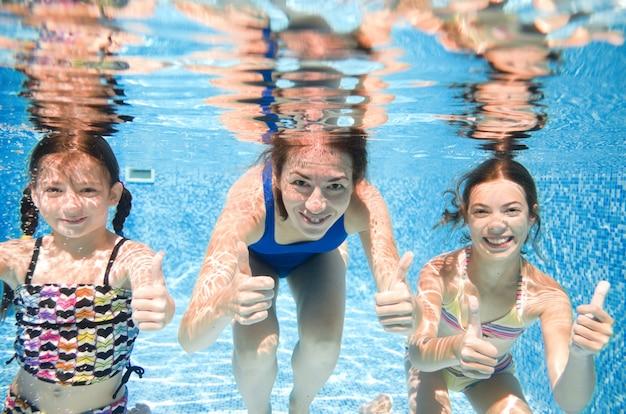 Familie zwemt in het zwembad onder water, gelukkige actieve moeder en kinderen hebben plezier onder water, fitness en sport met kinderen tijdens de zomervakantie