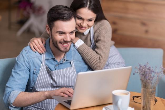 Familiebedrijf. mooie vrouw en positieve knappe man glimlachend en met behulp van laptop zittend in een fauteuil.
