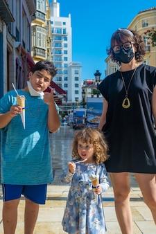 Familiebeeld op calle larios die ijs eet tijdens de pandemie in de zomer