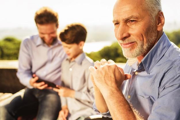 Familiebijeenkomst in park. oude man gevouwen handen.