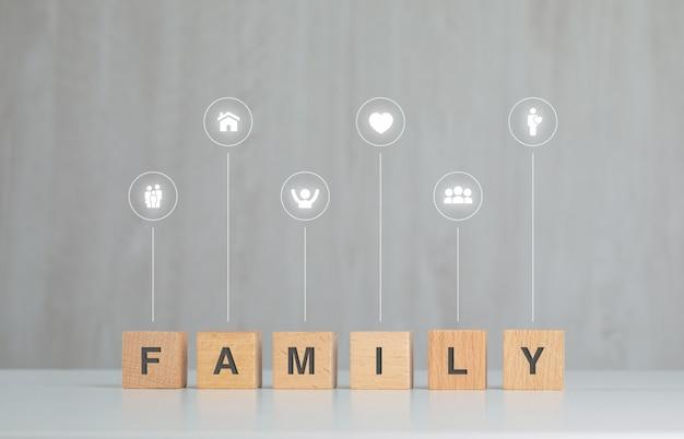 Familieconcept met houten kubussen, pictogrammen op grijs en wit lijst zijaanzicht.
