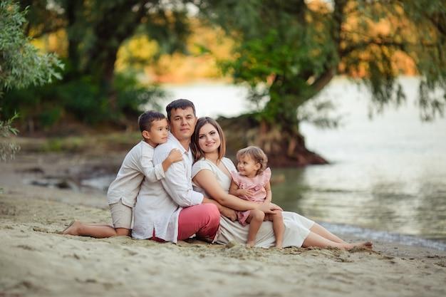 Familiedag, gelukkige ouders. moeder, vader, zoon en dochter hebben plezier tijdens een wandeling. ze zitten op het zand bij de rivier
