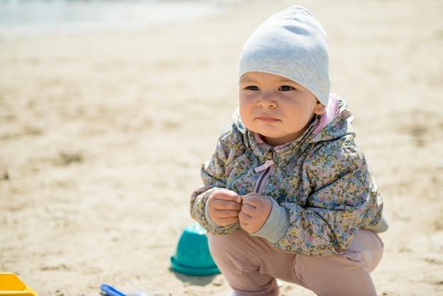Familiedag in het park. gelukkig jong koppel met pasgeboren baby. moeder draagt baby in ergonomische draagzak