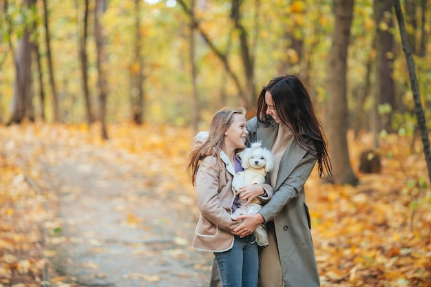 Familiedag met jonge moeder en meisje in de herfstpark in oktober