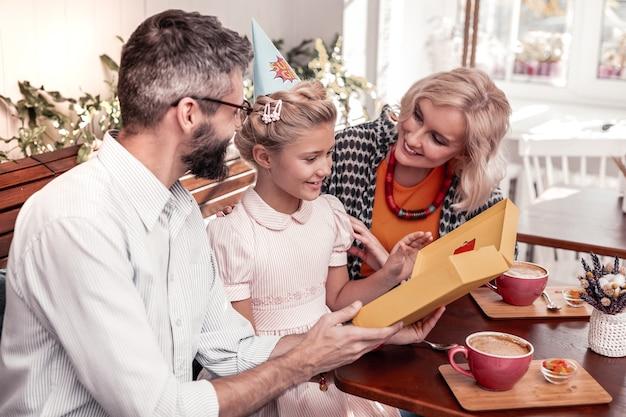 Familiefeest. blij leuk meisje lachend tijdens het vieren van haar verjaardag met ouders
