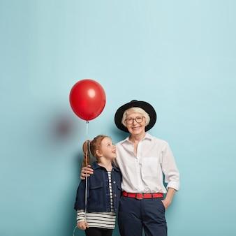 Familiefeest concept. schattige roodharige meisje feliciteert volwassen oma met moederdag, houdt rode luchtballon, omhelzen samen, geïsoleerd over blauwe muur met lege ruimte.