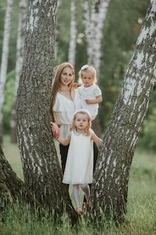 Familiefoto-moeder met dochters in het park. foto van jonge moeder met twee schattige kinderen buiten in het voorjaar, mooie vrouw met dochter plezier