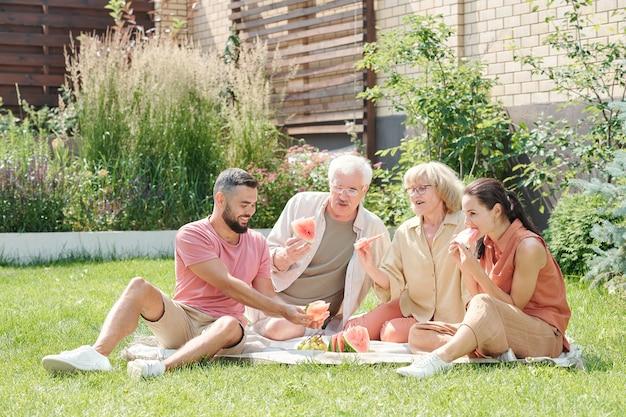 Familiefoto van moderne senior man en vrouw die picknicken met hun volwassen kinderen op het gazon