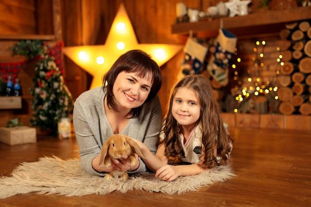 Familiefoto van moeder en dochter die op de vloer bij open haard met leuk konijn leggen. kerst decoratie
