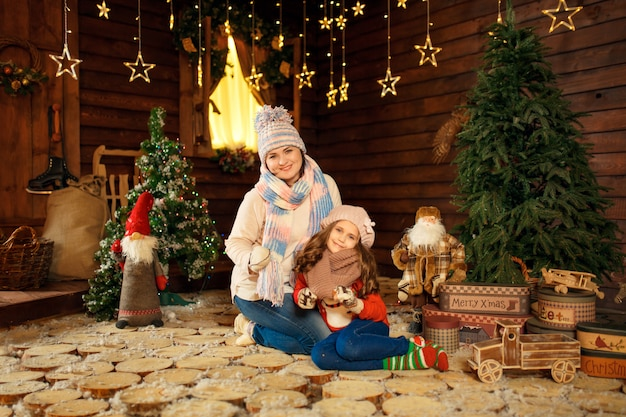 Familiefoto van moeder en dochter die op de vloer met leuk konijn leggen. kerst decoratie