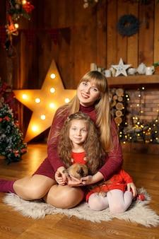 Familiefoto van moeder en dochter zittend op de vloer met schattig konijn. kerst decoratie