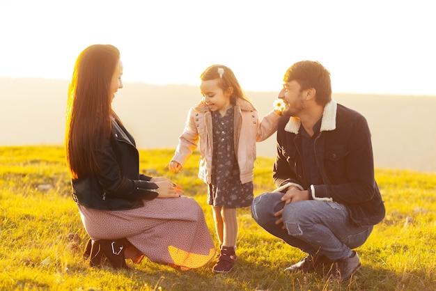 Familiefoto van ouders en meisje met tijd in park of veld op zonsondergang