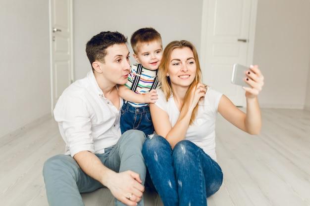 Familiefoto van twee jonge ouders die met hun jongenskind spelen