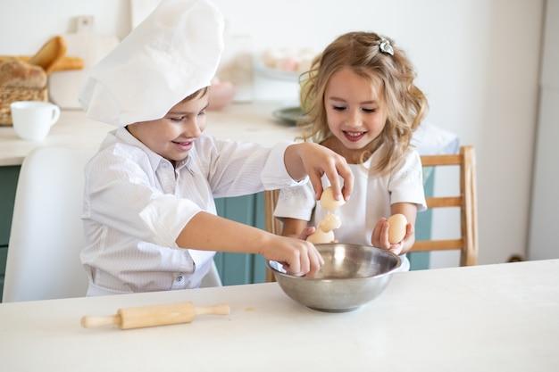 Familiejonge geitjes in witte chef-kok eenvormig voorbereidend voedsel op de keuken