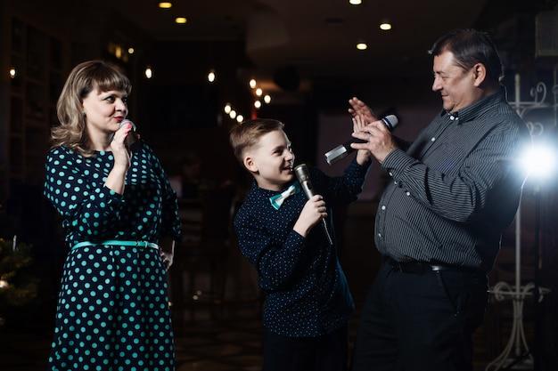 Familiekaraoke, portret van een gelukkig gezin, zingen in microfoons