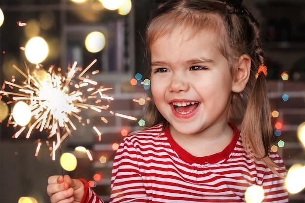 Familiekerstmis thuis. leuk klein meisje dat in kerstmanhoed brandend sterretje houdt en gelukkig glimlacht