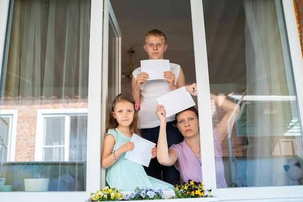 Familiekindmeisje met moedervrouw en tienerjongen uit het raam toont een wit blanco vel voor een bericht met een kopieerruimte tijdens de thuisisolatie van de coronaviruspandemie