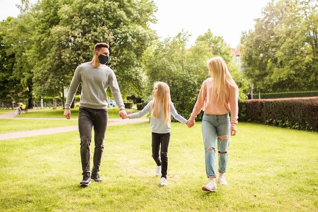 Familieleden die in het park lopen die de maskers van het stoffengezicht dragen.