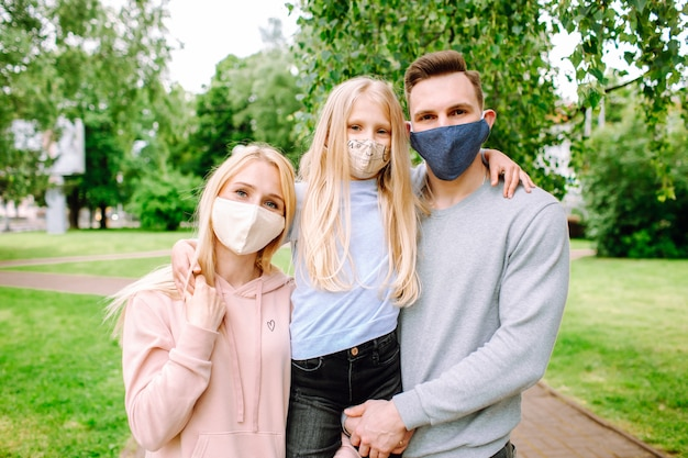 Familieleden omhelzen elkaar, glimlachen en dragen stoffen gezichtsmaskers