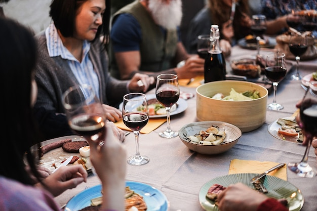 Familiemensen die plezier hebben tijdens het barbecuediner - multiraciale vrienden die eten bij een bbq-maaltijd buiten - eten, vriendschap, verzamelen en zomerlevensstijlconcept - focus op het middelste wijnglas