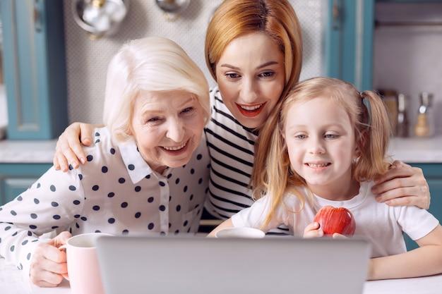 Familieoproep. drie generaties vrouwen zitten aan het aanrecht en glimlachen naar de webcamera terwijl ze een videogesprek voeren met iemand