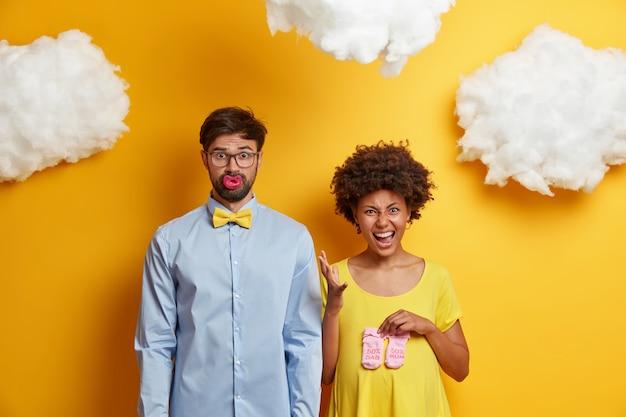 Familiepaar bereidt zich voor om ouders te worden die met babyspullen tegen de gele muur poseren. emotionele zwangere afro-amerikaanse vrouw houdt sokken voor baby over buik. toekomstige bebaarde vader zuigt tepel