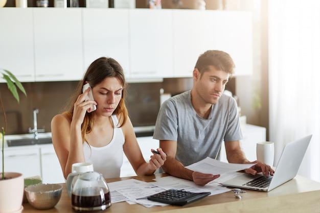 Familiepaar dat financiële problemen heeft, probeert ze op te lossen, lening gaat aannemen, bank belt, contract ondertekent. man en vrouwenzitting bij keuken die moderne apparaten voor hun bedrijfswerk gebruiken