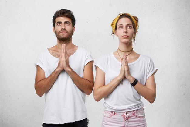 Familiepaar dat samen bidt voor de gezondheid van hun kind. jonge, bebaarde man en schattige vrouw in witte t-shirts houden hun handen bij elkaar terwijl ze bidden en kijken omhoog met ogen vol hoop op beter