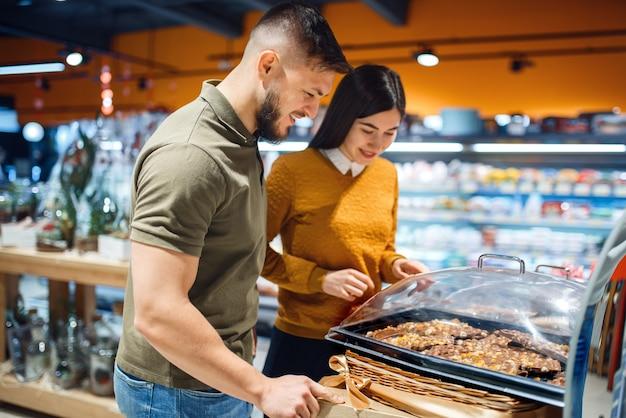 Familiepaar dat taarten kiest in de supermarkt, snoepafdeling