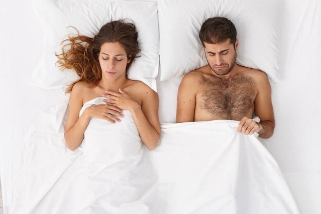 Familiepaar heeft een probleem van onvruchtbaarheid, de man kijkt neer onder een deken, heeft erectiestoornissen en impotentie, een droevige vrouw ligt dichtbij, kan geen kind krijgen. seksuele gezondheid, geslachtsziekte concept.