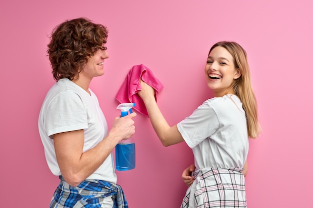 Familiepaar heeft positieve gezichtsuitdrukkingen, gebruikt vodden en spray om het appartement schoon te maken