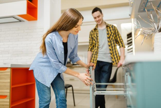 Familiepaar in de toonzaal van de meubelwinkel. man en vrouw kijken naar kast in winkel, man en vrouw kopen goederen voor modern interieur