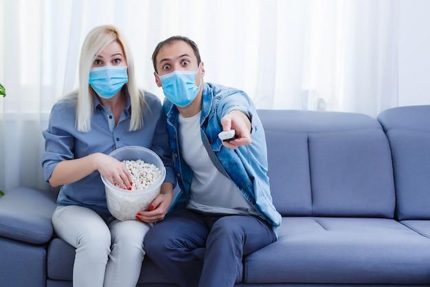 Familiepaar met medische gezichtsmaskers liggend op een bed met een laptop. concept van video kijken, samenwerken en quarantaine tijdens een covid-19 coronavirus-epidemie